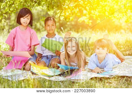 Group of kids playing and tinkering in the garden in summer on a blanket