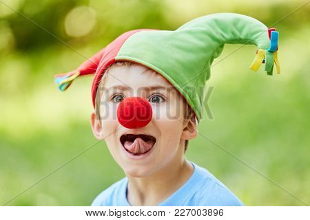 Boy with red nose and fool's cap in the carnival sticks out his tongue