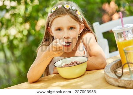 Hungry girl is eating healthy cereal for breakfast in kindergarten