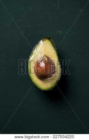 high angle view of half ripe avocado with its pit wrapped in plastic wrap, on a dark greeen surface with some blank space around it