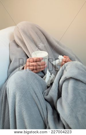 closeup of an ill young caucasian man at home, covered with a light gray soft blanket, warming up with a cup of hot milk