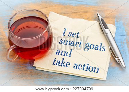 I set smart goals and take action - positive handwriting on a anapkin with a cup of tea