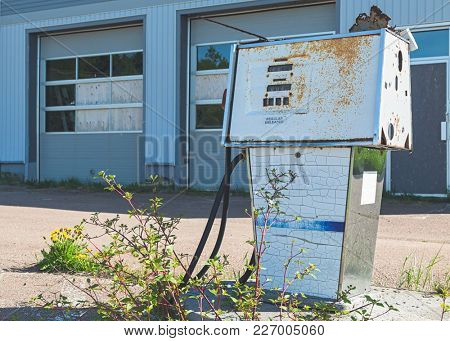 Weathered gas pump in a long abandoned gas station.