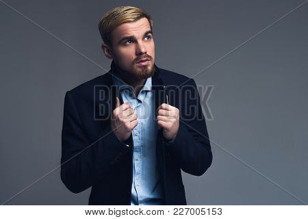 Serious And Professional. Young Business Man Holding Lapels Standing And Watching Up In Front Of Gre