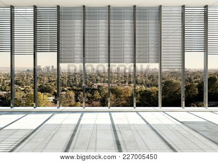 Large spacious unfurnished room with glass window wall and Venetian blinds overlooking a city with greenery and trees. 3d Rendering.