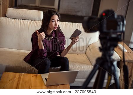 Pretty Young Dolly-girl Vlogger Sitting On The Sofa With Her Smartphone And Laptop And Keeping A Blo
