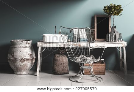 Old rustic vintage style bathroom interior with a wire work chair, grungy wooden table, old fashioned plumbing and ceramic urns on a tiled floor. 3d rendering