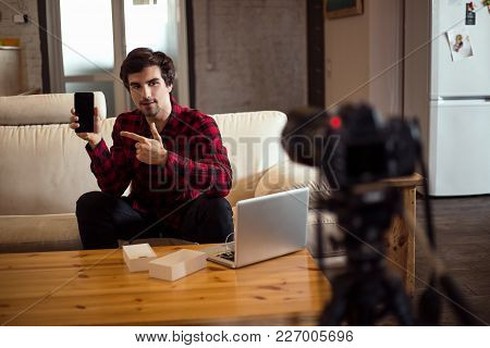 Young Smart Bearded Man Making A Video For His Own Blog And Advertising The Smartphone While Sitting