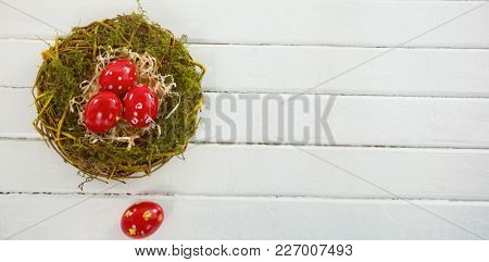 Close-up of red Easter eggs in nest on wooden table