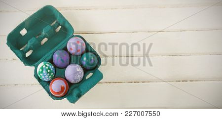 Multicolored Easter eggs in carton on wooden background