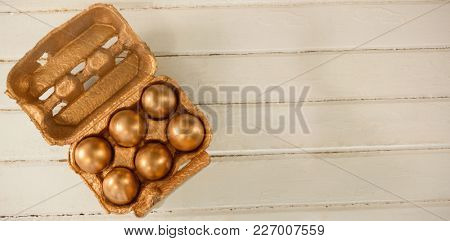 Golden Easter eggs in carton on wooden background