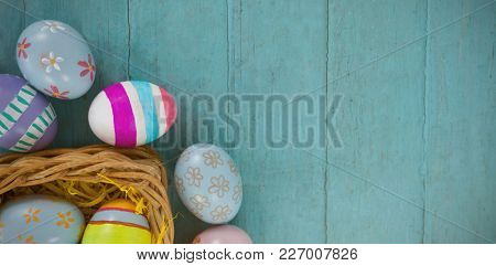 Various Easter eggs arranged in wicker basket on wooden surface