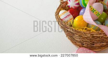Various Easter eggs with ribbon in wicker basket on white background