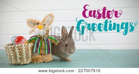 Easter greeting against easter eggs on wicker basket with easter bunny and toy