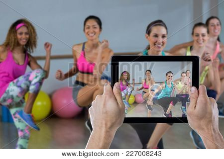 Cropped hand holding digital tablet against group of women performing aerobics