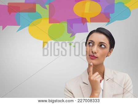 Digital composite image of businesswoman looking at speech bubble icons