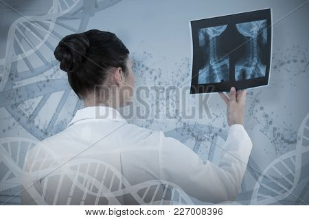 Female doctor checking x-ray report against device screen of dna helix pattern