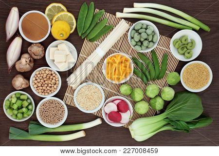 Macrobiotic diet food with japanese udon noodles, tofu, miso and wasabi paste, grains, legumes, vegetables and wasbai nuts with foods high in protein, antioxidants, fibre, vitamins and minerals.