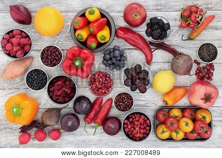 Healthy eating super food concept with fruit, vegetables, pulses and grains very high in anthocyanins, antioxidants, minerals and vitamins on rustic wood backgorund. Top view.