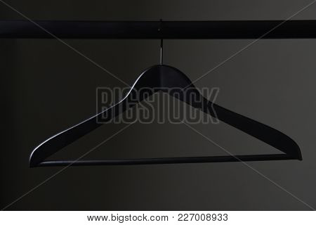 A black coat hanger and closet rod against a light to dark gray background.