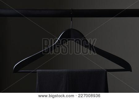 A pair of mens dark slacks hanging on a black hanger and closet rod, set against a light to dark gray background.