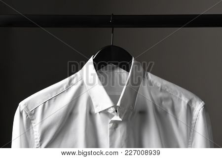 Closeup of a white dress shirt on a black hanger and closet rod against a light ot dark gray bakground.