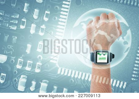 Cropped hand wearing watch against globe in circuit board