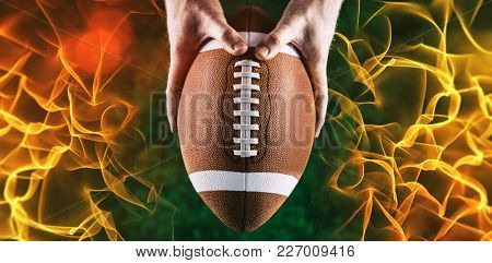 American football player holding up football against abstract orange glowing black background