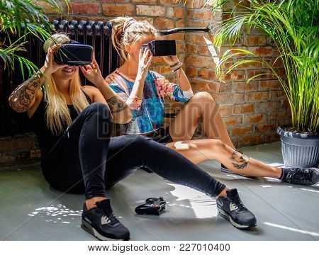 Two Blond Females Sitting On The Floor And Having Fun With Virtual Reality Glasses.