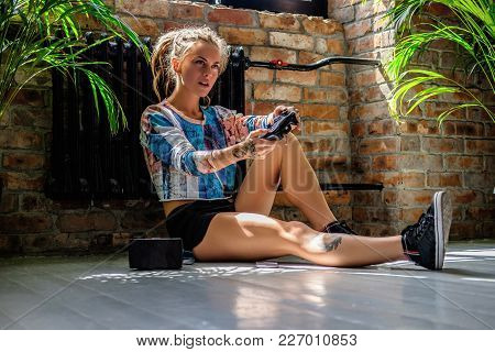 Attractive Blond Female Sitting On A Floor And Using Virtual Reality Device.