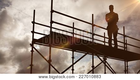 Portrait of happy repairman standing arms crossed against blue sky with white clouds