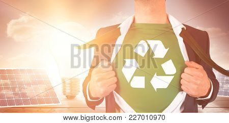 Businessman opening shirt in superhero style against light bulb and solar panels on floorboards in sky