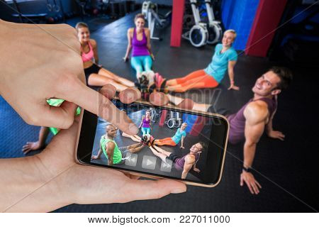 Portrait of smiling of friends in gym against hands touching smart phone