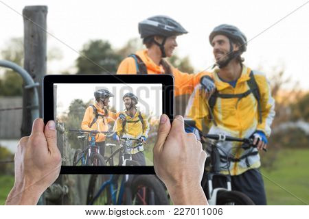 Cropped hand holding digital tablet against biker couple interacting while standing with mountain bike