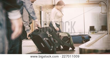 People carrying luggage from baggage claim at airport
