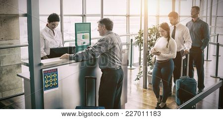 People waiting in queue at airplane counter at airport
