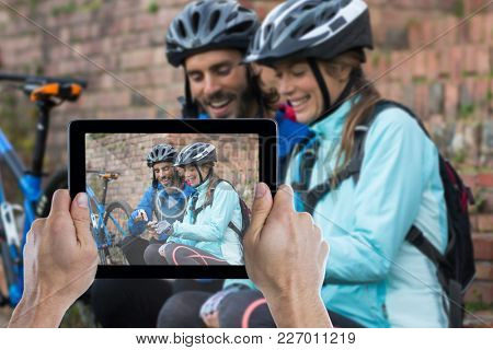 Cropped hand holding digital tablet against biker couple using mobile phone
