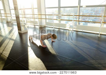 Marketer Practice Physiotherapy In Spacious Gym, Guy Lie On Parquet Floor Rock Press. Fair-haired Ta