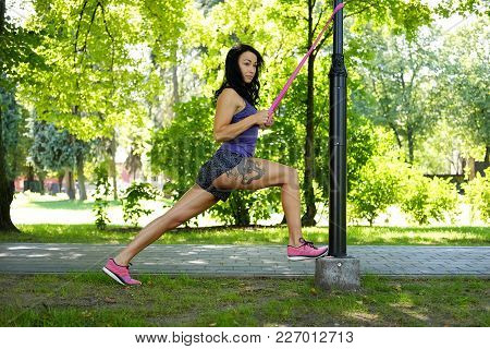 Sporty Female With Tattoo On Her Leg Doing Exercising With Fitness Trx Straps In A Summer Park.