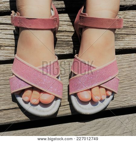 Glitter Pink Sandals In The Feet Of A Girl