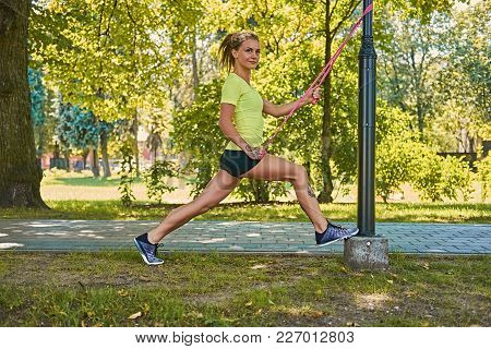 Slim Blonde Female Doing Workouts With Fitness Trx Strips In A Park.