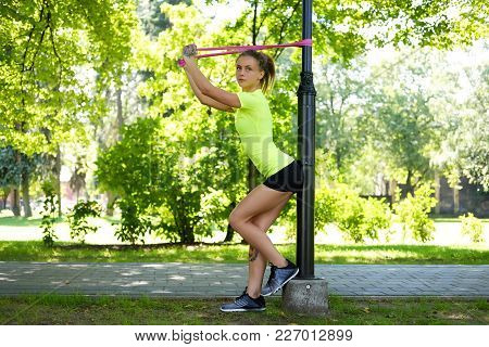 Athletic Blond Female Exercising With Fitness Trx Straps In Summer Park.