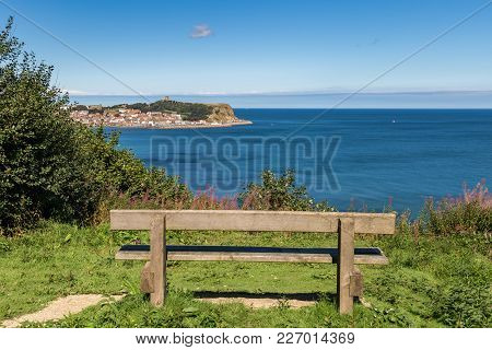 A Wooden Bench With View Over The North Sea And Scarborough, North Yorkshire, Uk