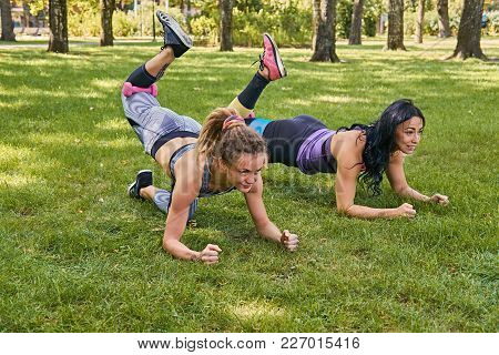 Two Women Doing Legs Workouts On A Grass In A Park.