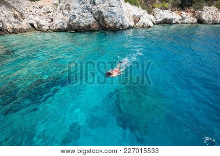 Young Woman Snorkeling In The Turquoise Water In Agistri, Greece