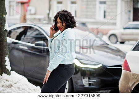 Stylish African American Plus Size Model With Mobile Phone Against Electro Car.