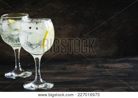Alcohol Drink (gin Tonic Cocktail) With Lemon And Ice On Rustic Black Wooden Table, Copy Space, Top