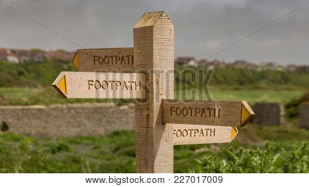 Sign: Footpath, Pointing In All Directions, Seen In Tide Mills Near Seaford, East Sussex, Uk