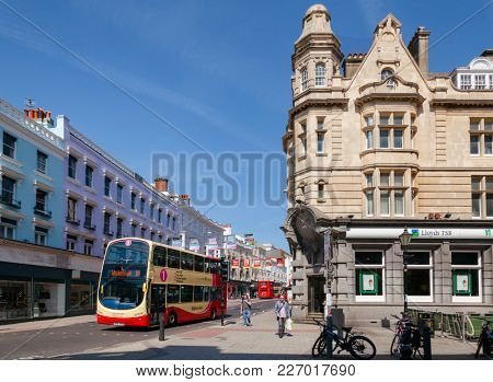 BRIGHTON, UK - JUN 5, 2013: Double Decker bus moves along the North Street near Royal Pavilion entrance