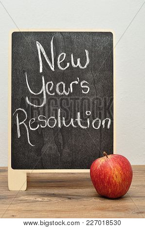 A Black Board With The Words New Years Resolution And An Apple